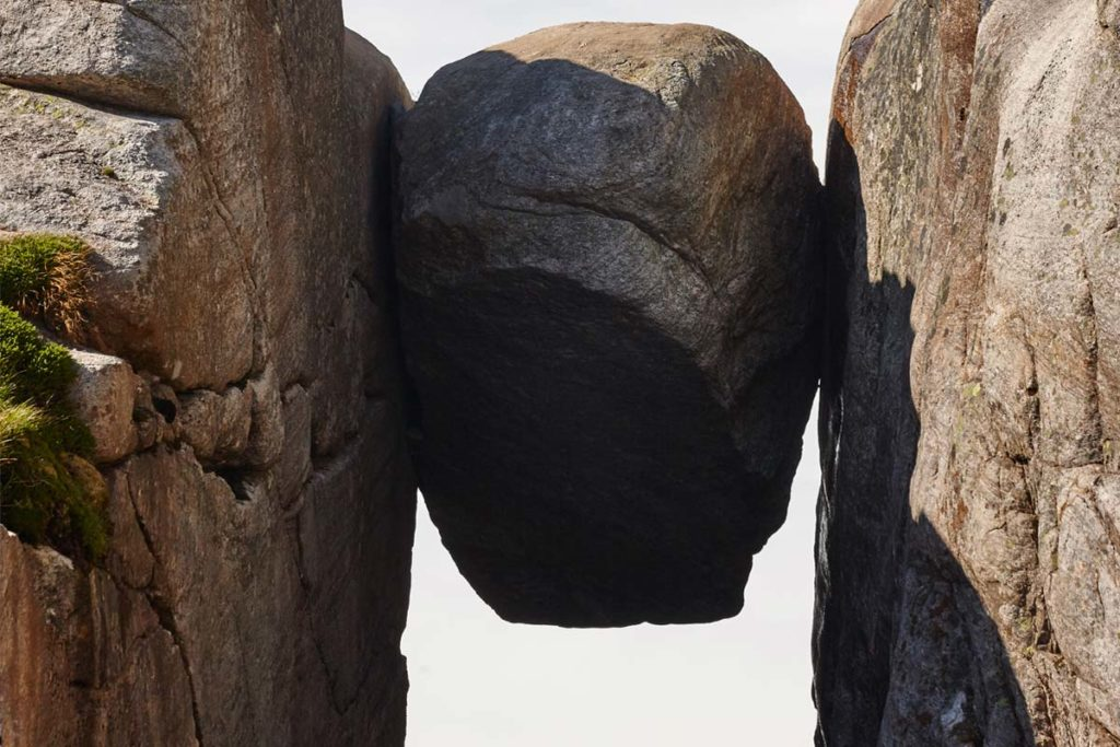 A heavy boulder sits lodged between two cliffs, suspended overhead.